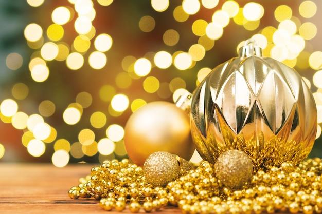 ぼやけている光沢のあるボケ背景に木製のテーブルでクリスマスボール