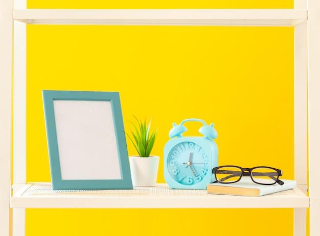 明るい黄色の背景に文房具オブジェクトの白い棚
