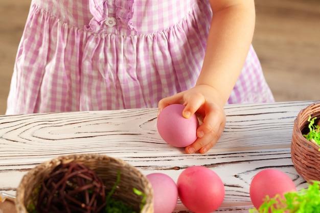 Рука маленькой девочки держа покрашенное пасхальное яйцо. заделывают выстрел