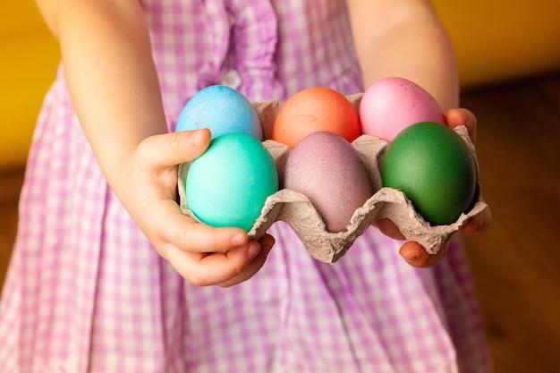 Маленькая девочка держит корзину с крашеные яйца. пасхальная концепция