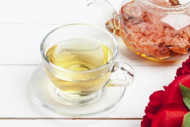Стеклянный чайник травяного чая со свежими цветами крупным планом