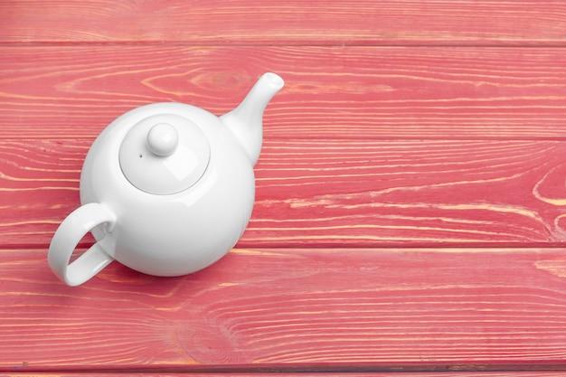 Белый керамический чайник на деревянном столе крупным планом
