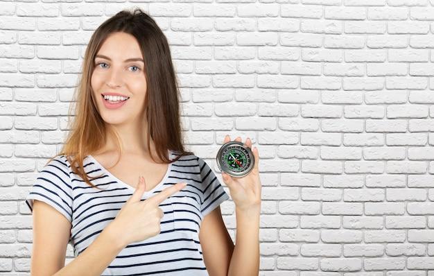 美しい若い女性は彼女の顔の近くにコンパスを持っています。概念