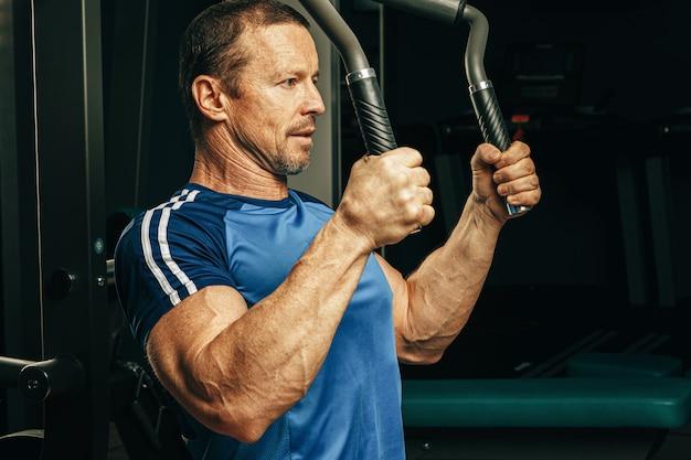 ジムのトレーニングマシンで腕の演習を行うシニア男性