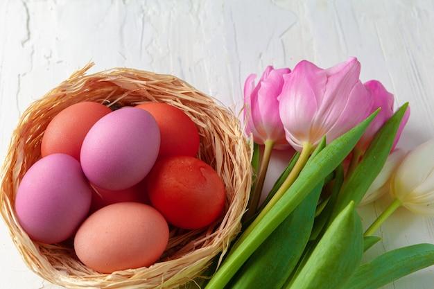 Пасхальная композиция с тюльпанами и корзиной из крашеных яиц
