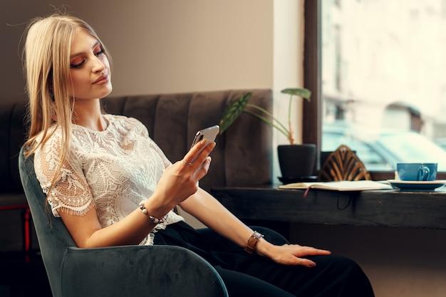 食堂に座っている間彼女のスマートフォンを使用して幸せな若い女