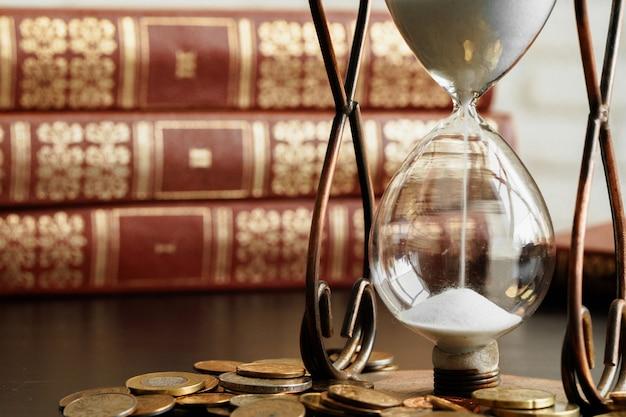 時間はお金の概念です。お金のコインで砂時計のクローズアップ