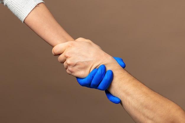 青い手袋で握手、コンセプトを助けます。