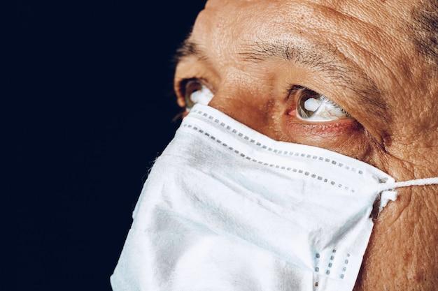 医療マスクで病気の成人男性の肖像画をクローズアップ。コロナウイルスのパンデミアのコンセプト