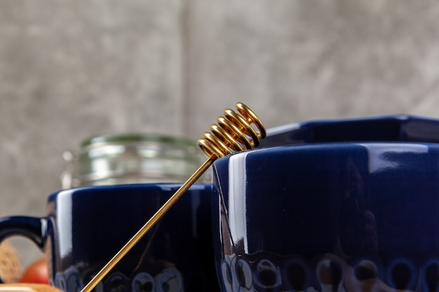 Фото натюрморта пустой чашки чая с ложкой меда. кухонный стол крупным планом