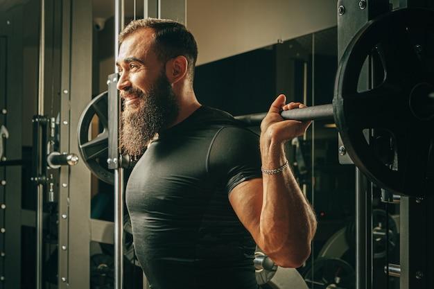 トレーニングマシンでスクワットをしている男性に合う