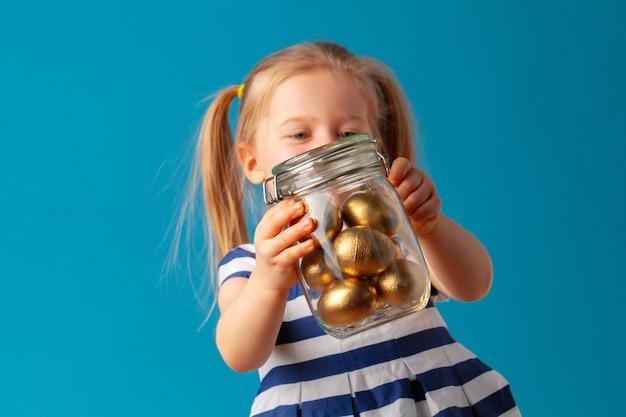Маленькая милая девушка держит стеклянную банку с золотыми яйцами, окрашенными на пасху