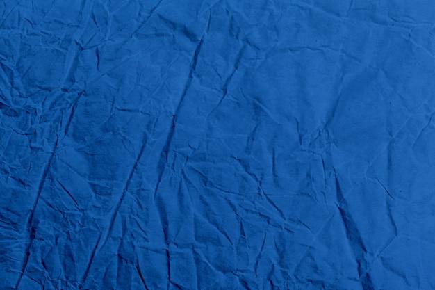 背景としてしわくちゃの古典的な青い布