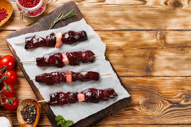 野菜と木製の背景に肉から生のケバブ。