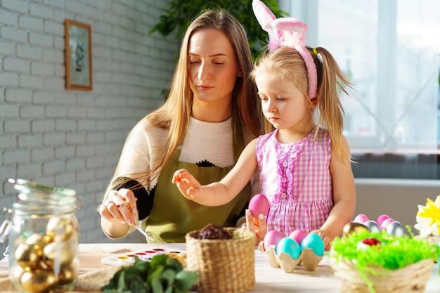 かわいい家族、母と娘がイースターのお祝いの準備
