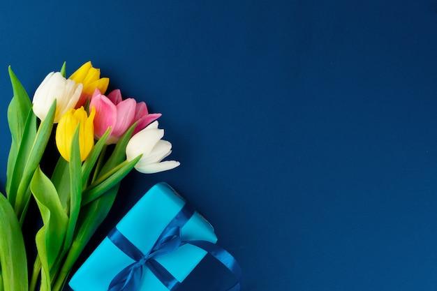 Свежие цветы и подарочная коробка с лентой