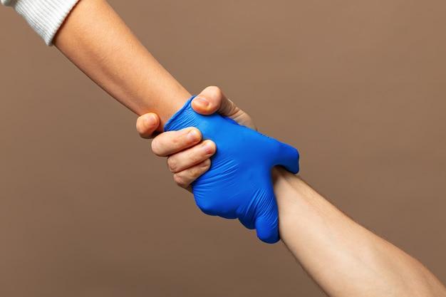 青い手袋で握手、コンセプトを助けます。パンデミック時の個人衛生