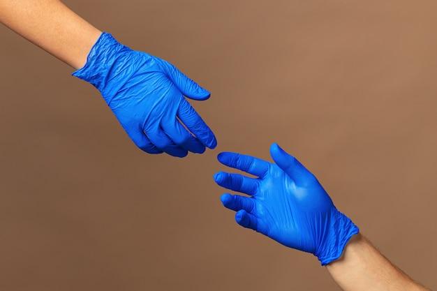医療用手袋の男性と女性の手がお互いに伸びます。ヘルプの概念。