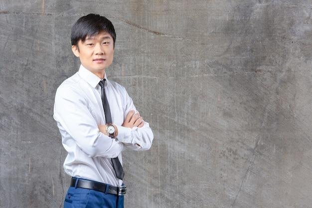 Красивый молодой азиатский человек стоя носящ костюм