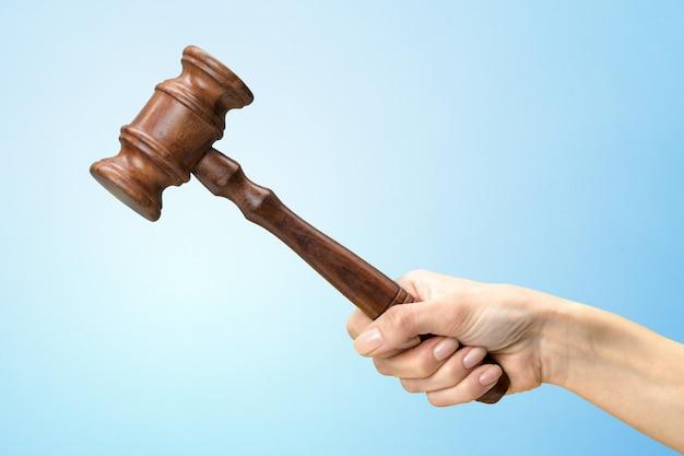 Кто-то рука держит деревянный закон молоток