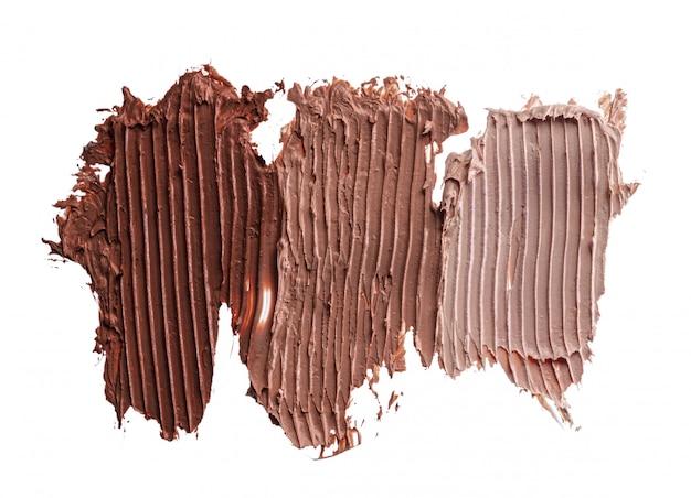 白で隔離される濃いクリーム色の化粧品ファンデーションの塗抹標本