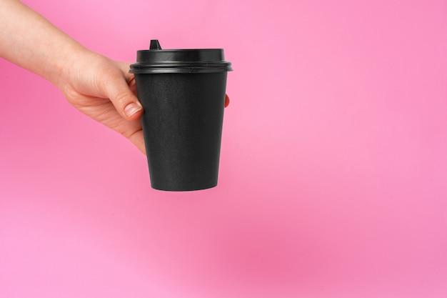 コーヒーの配達。持ち帰り用のコーヒーカップを持っている人間の手