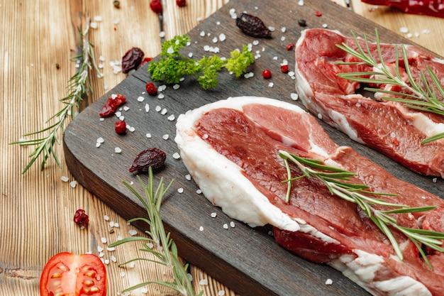 木の板にハーブと生肉ステーキ