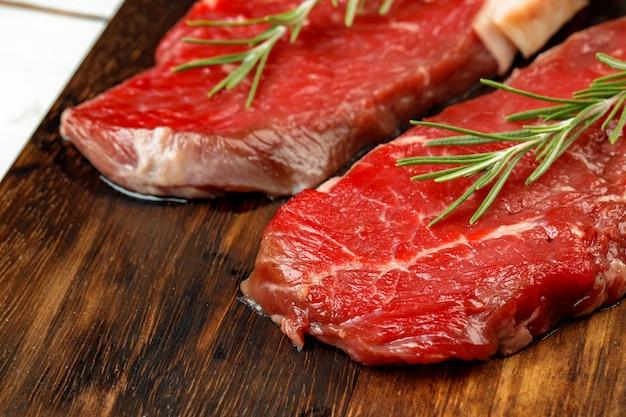 木の板にローズマリーとバーベキューの子牛のステーキ