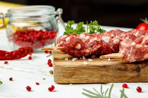 Сырье люля кебаб на шпажках со специями на деревянной доске