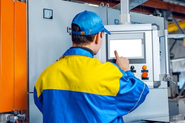 ケーブル工場の機械制御コンピューターパネルで製造工場の男性労働者