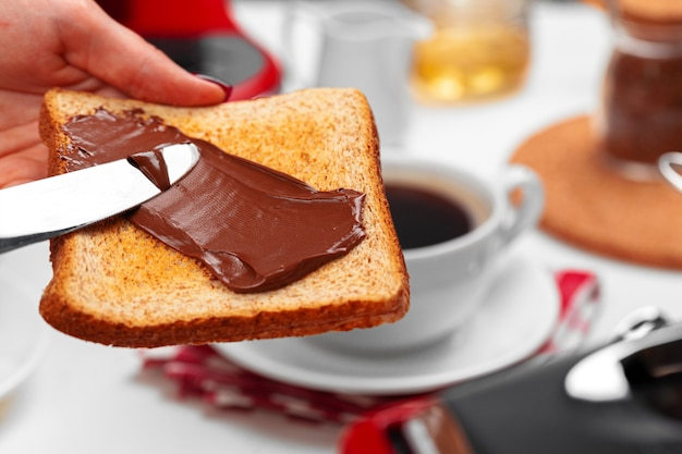Женская рука готовит тост с шоколадной пастой