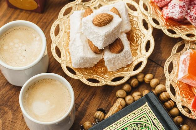 木製のテーブルに東洋のお菓子とコーヒーカップ