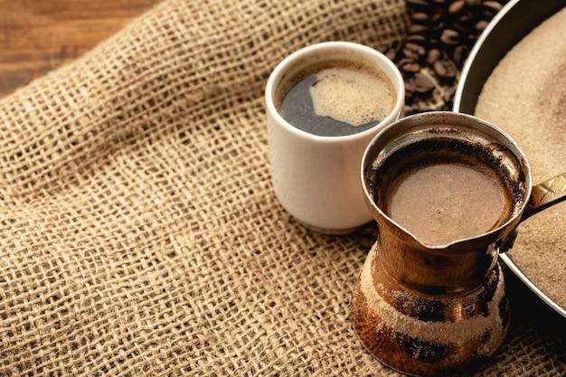 Белая кофейная чашка с жареными бобами на вретище