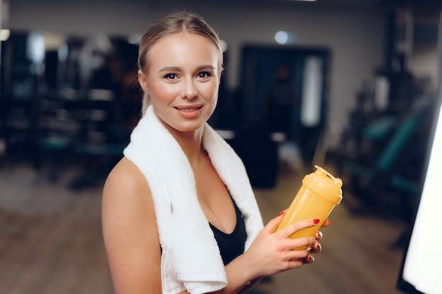 Привлекательная положительная женщина с полотенцем и бутылкой с водой в спортзале
