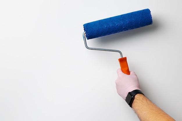 手袋をはめた男性の手の壁をクラシックなブルーの色に