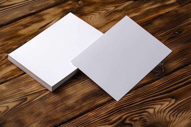 Стопка белых визиток на коричневом деревянном фоне