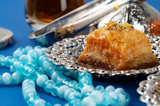 Турецкий десерт в металлической традиционной тарелке на синем
