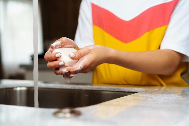 台所の流しで手を洗う女性のクローズアップ