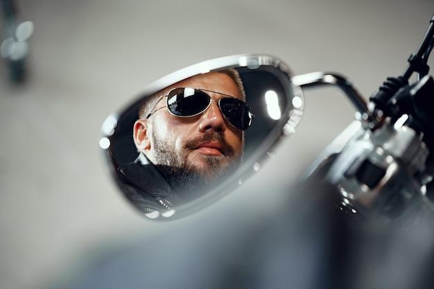サングラスをかけた男性ドライバーのオートバイミラーの反射
