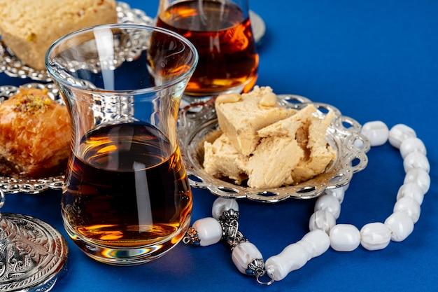 Халва десерт с чашкой чая на синем фоне