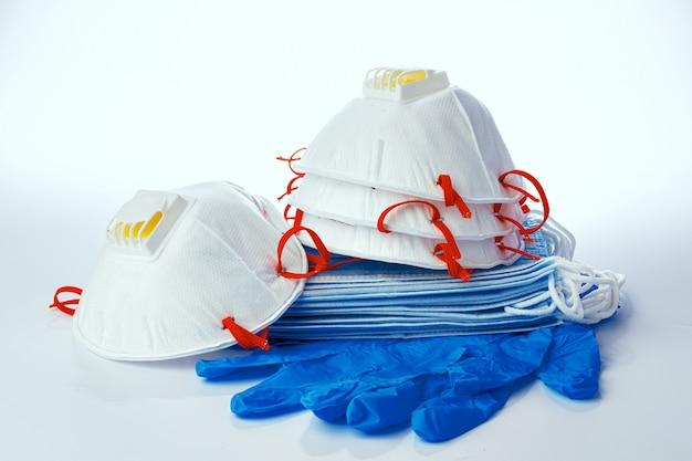 Медицинские маски со стерильными латексными перчатками на белом фоне