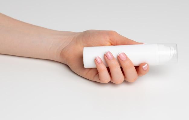 Женская рука держит косметическую бутылку на белом