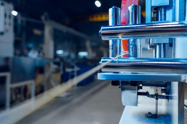 電力用電気ケーブルと光ファイバーを生産する近代的な工場の内部。 。ケーブル製造機械部品。