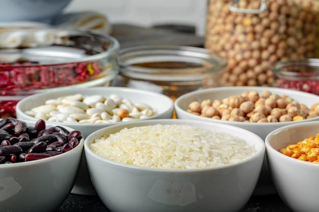 キッチンテーブルの上の穀物の盛り合わせと白いセラミックボウル