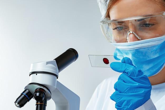 Женщина-ученый, глядя на слайд с образцом крови возле микроскопа в лаборатории