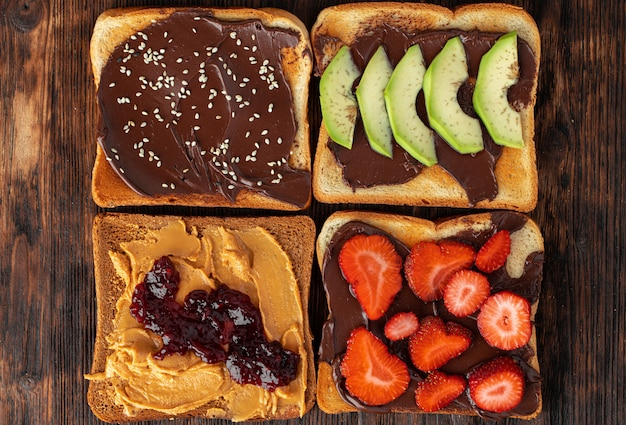 Ассорти из сладких бутербродов с шоколадной пастой, арахисовой пастой и кусочками фруктов