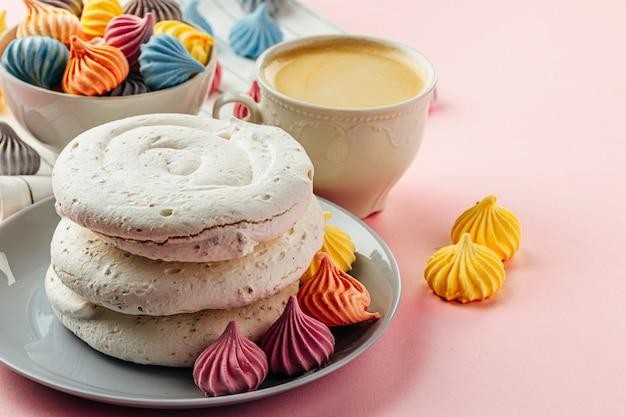 カラフルなミニメレンゲとピンクの背景に白いメレンゲクッキー