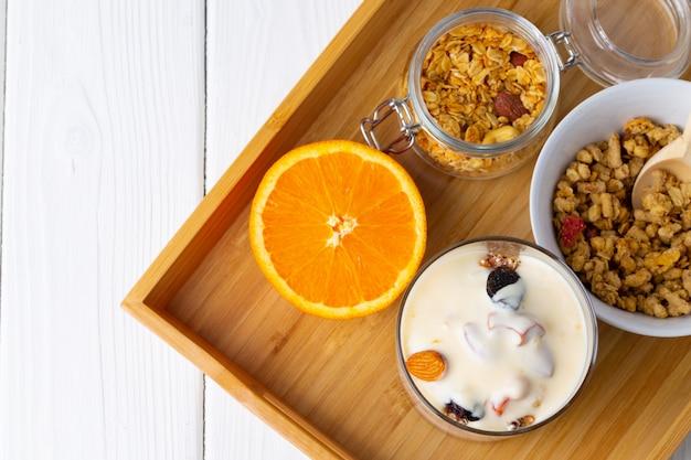 Вкусный завтрак с мюсли, йогуртом и фруктами в стеклянной миске
