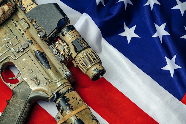 米国のバトルフラグと木製のテーブルのアサルトライフル。