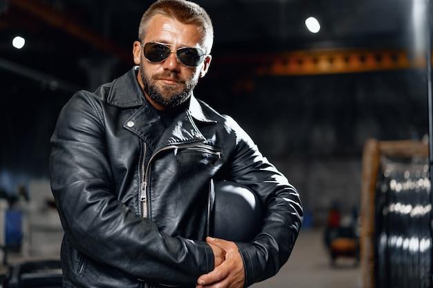 Портрет бородатого мотоциклиста в темных очках на темном фоне